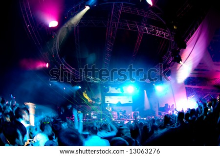 People having fun at the concert, laser show and music - stock photo