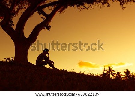People having problems concept. Silhouette of sad and lonely man sitting alone under a tree.