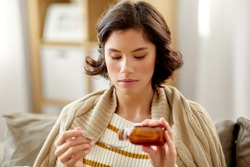 people, health and medicine concept - sad sick young woman in blanket pouring antipyretic or cough syrup from bottle to spoon at home