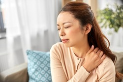 people, health and problem concept - tired asian woman suffering from ache in neck at home