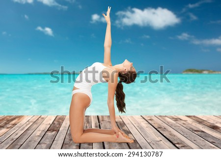 people, health and wellness concept - woman in cotton underwear doing yoga exercise on wooden floor over sea and blue sky background