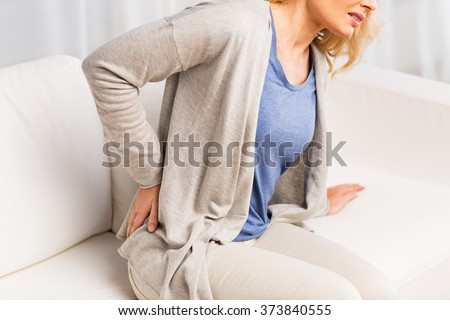 people, healthcare and problem concept - close up of unhappy woman suffering from pain in back or reins at home