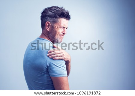 People, healthcare and problem concept - unhappy man suffering from neck or shoulder pain at home ストックフォト ©