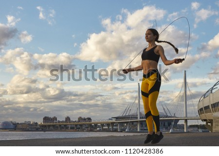 People, healthy lifestyle, activity, sports and fitness concept. Picture of happy endurant sporty girl with long braid jumping with skipping rope outdoors, practicing endurance and stamina #1120428386