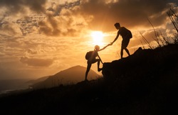 People helping each other concept. Man helping woman up the edge of a mountain.