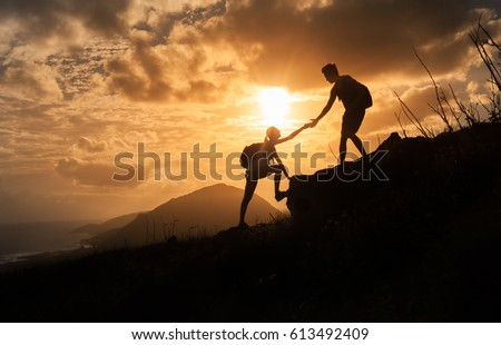 People helping each other concept. Man helping woman up the edge of a mountain.   #613492409