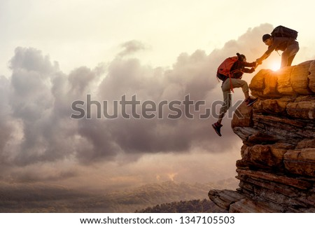 People helping each other hike up a mountain at sunrise. Giving a helping hand, and active fit lifestyle concept.Asia couple hiking help each other.