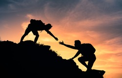 People helping each other up a mountain. Helping hand and teamwork concept.