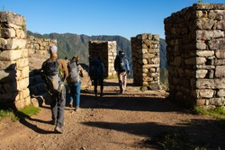 People hiking in the Andes in Inka Trail enroute to Macchu Picchu passing through some of the ruins.