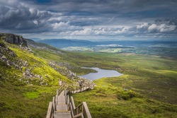 People hiking on steep stairs of wooden boardwalk in Cuilcagh Mountain Park. View on lake and valley below with dramatic sky, Northern Ireland