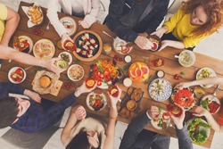 People hold glasses and eat healthy meals at party dinner table. Friends celebrate with organic food, ratatoille and corn barbecue on wooden table top view.