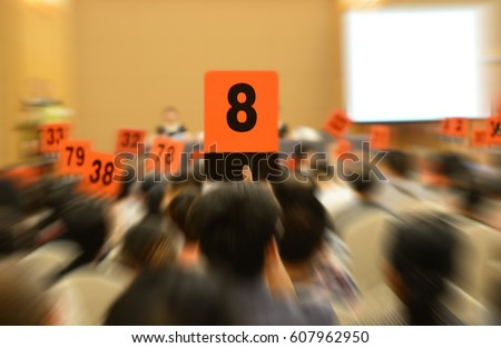 People holding auction paddle to buy from auction.