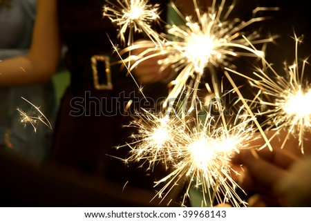 People holding beautiful sparklers (fire crackers) in hands on a birthday, Christmas or New Year party. Useful file for the upcoming holidays and parties.