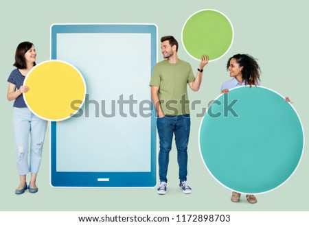 People holding geometric icons in front of a  paper cutout of a tablet #1172898703