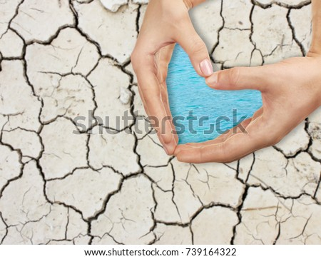 People holding hands in shape of heart and dry soil on background. Concept of water conservation #739164322