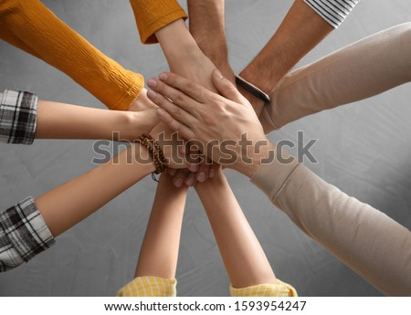People holding hands together over grey stone background, top view. Unity concept