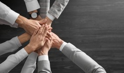 People holding hands together over grey wooden background, top view. Unity concept