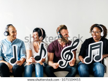 People holding musical icons