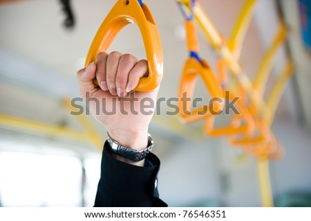 people holding onto a handle on a train.