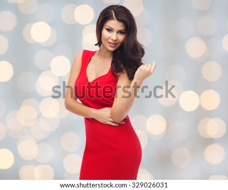 Stock Photo people, holidays and fashion concept - beautiful sexy woman in red dress over lights background