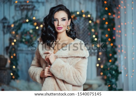 people, holidays and glamour concept - beautiful woman with makeup in fur coat and gold earrings over blue lights background. Merry Christmas party. New year miracle