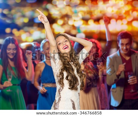 people, holidays and nightlife concept - happy young woman or teen girl in fancy dress with sequins and long wavy hair dancing at night club party over crowd and lights background