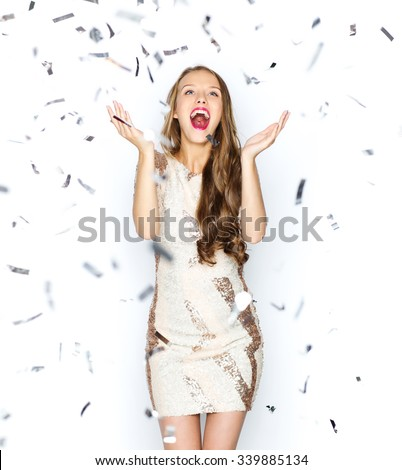 people, holidays, emotion and glamour concept - happy young woman or teen girl in fancy dress with sequins and confetti at party