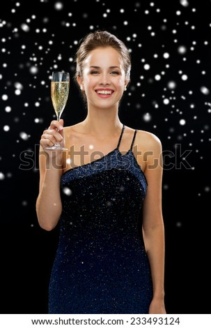 people, holidays, luxury and celebration concept - smiling woman holding glass of sparkling wine over black snowy background