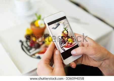 people, holidays, technology, food and lifestyle concept - close up of woman with smartphone taking picture of dessert at restaurant