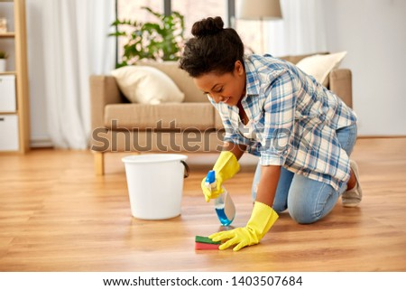 people, housework and housekeeping concept - african american woman in rubber gloves with sponge and detergent cleaning floor at home #1403507684
