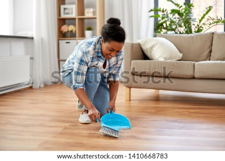 people, housework and housekeeping concept - african american woman with brush and dustpan sweeping floor at home #1410668783