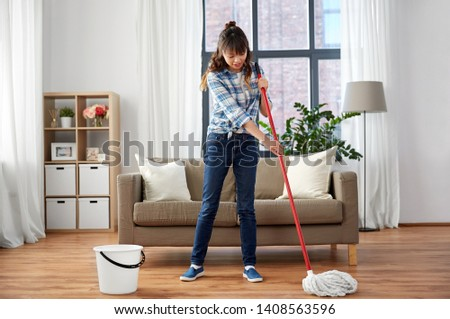 people, housework and housekeeping concept - happy asian woman with mop and bucket cleaning floor at home #1408563596