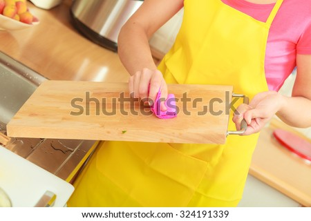People, housework and housekeeping concept. Woman doing the tidying up in kitchen cleaning wooden cutting board with rag sponge #324191339