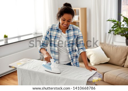 people, housework, laundry and housekeeping concept - happy african american woman in headphones ironing bed linen on board and listening to music at home #1410668786