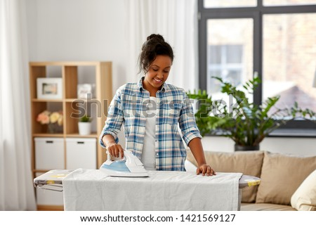people, housework, laundry and housekeeping concept - happy african american woman ironing bed linen on board at home #1421569127