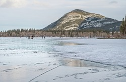 People ice skating and playing hockey on frozen Lac des Arcs in Alberta, Canada