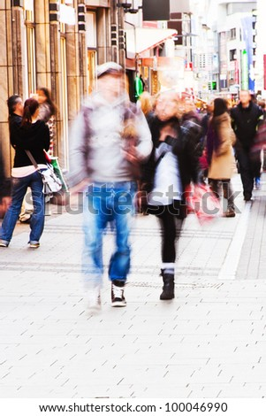 people imaged in motion blur walking in the city