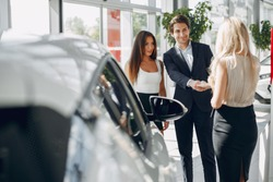 People in a car salon. Man buying the car. Elegant women with handsome man