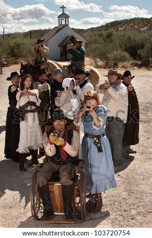 People in American old west scene with weapons in front of church