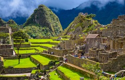 People in ancient Inca city of Machu Picchu, Peru panorama