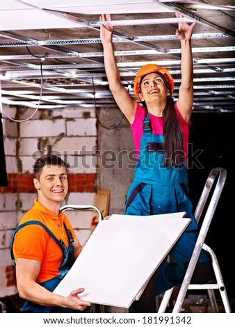 People in builder uniform installing suspended ceiling