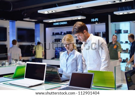people in consumer electronics  retail store looking at latest laptop, television and photo camera to buy