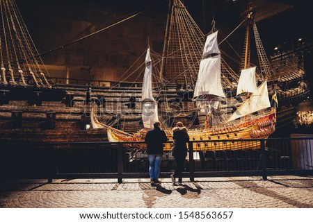 Photo of  People in front of model of Vasa, viking ship. The ship itself in the background
