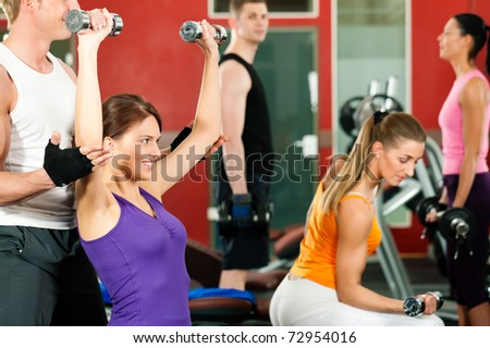 People in gym or fitness club exercising with weights together