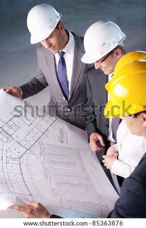 People in hard hats looking plan