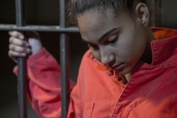People In Jail - Young woman looking sad holding onto the prison bars