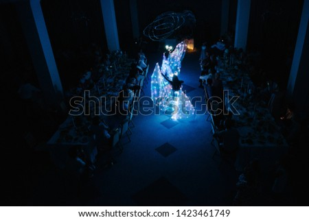People in luminous costumes dance in the dark for a holiday #1423461749
