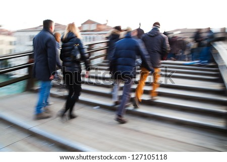 people in motion blur crossing the pedestrian bridge Ponte dell Accademia in Venice