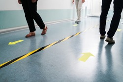 People In Office Following Social Distancing Tape Markings On Floor