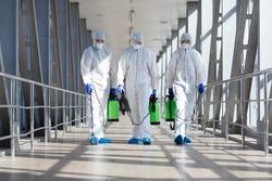 People in protective hazmat suits carrying barrels, pathogen respiratory quarantine coronavirus concept, copy space